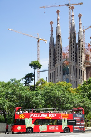 sagrada: BARCELONA, SPAIN - JUNE 9: Tourist bus near The La Sagrada Familia  June 9, 2011 in Barcelona, Spain.. La Sagrada Familia  designed by Gaudi, which is being build since 1882 and is not finished yet