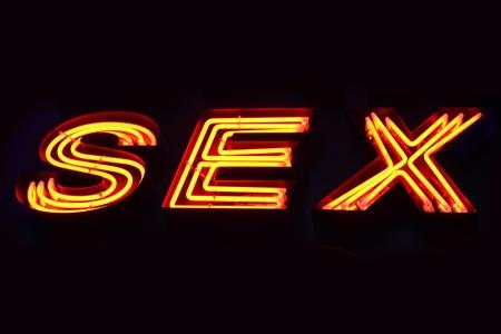 adult sex: Sex shop neon sign close-up over black background