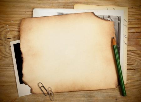 Stapel alter Papiere und Fotos auf einem Holztisch