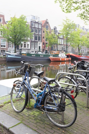 bike parking: Bicycles near canal in Amsterdam, Holland