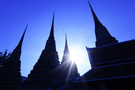 splendour: Silhouettes of stupas at Wat Pho temple, Bangkok, Thailand. Image toned in Blue.