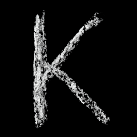 K - Chalk alphabet over black background photo