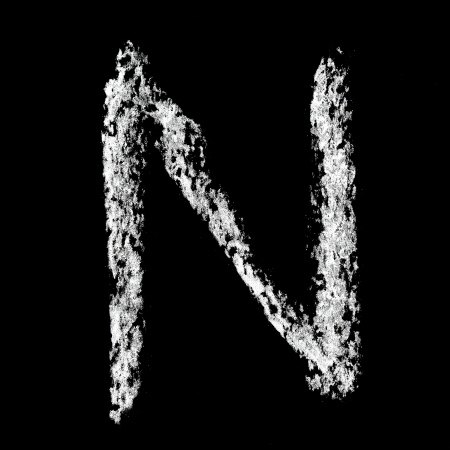 N - Chalk alphabet over black background photo