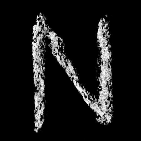 N - Chalk alphabet over black background photo