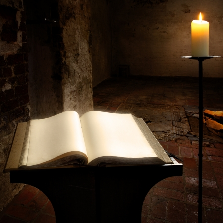 folio: Open book with blank pages and candle Stock Photo