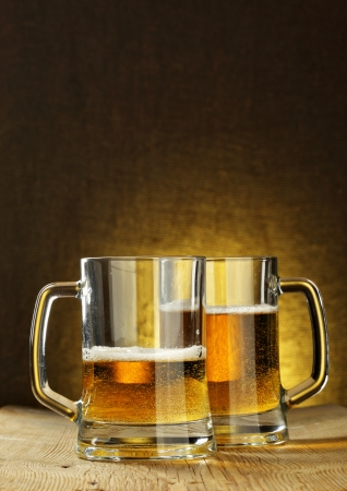Two beer mugs on wooden table photo