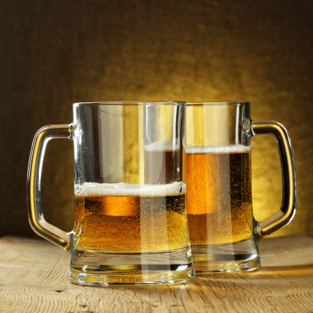 alehouse: Two beer mugs on wooden table Stock Photo