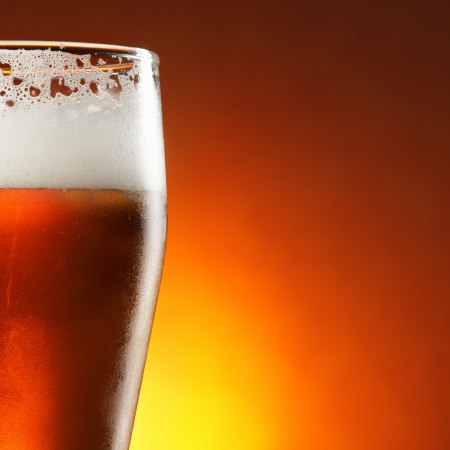 beer background: Glass of beer with froth close-up