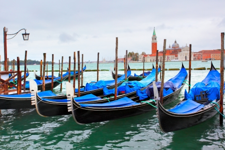 Gondolas near Saint Mark square and San Giorgio di Maggiore church in the background - Venice, Italy photo