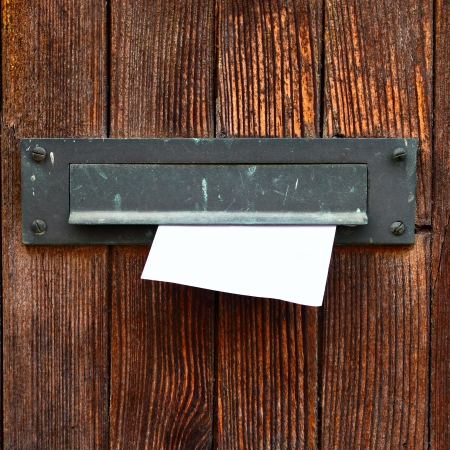 Letter box with envelope on wooden door photo