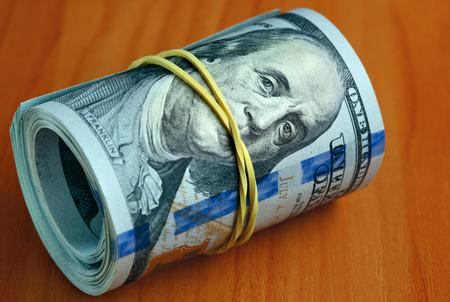 guardar silencio: Rollo de billetes de un d�lar en una mesa - Dinero a mantener el concepto en silencio