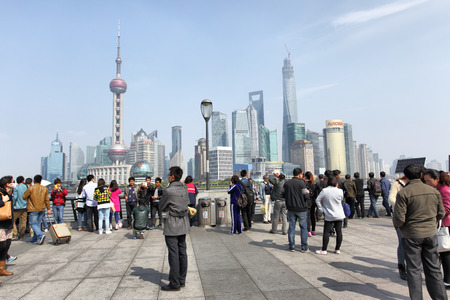 sightseeng: SHANGHAI, CHINA - APRIL 7, 2014  People on The Bund waterfront in Shanghai