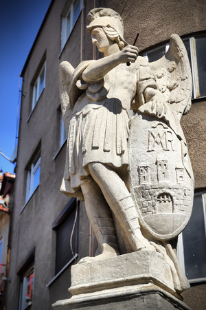 michael: Ancient statue of archangel Michael with emblem of Bratislava city on the shield, Slovakia Stock Photo