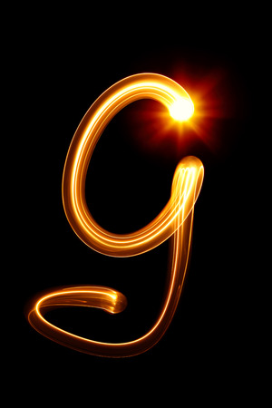 fire font: G - Created by light alphabet over black background Stock Photo
