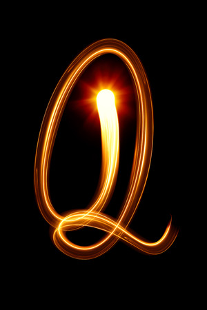 Q - Created by light alphabet over black background photo
