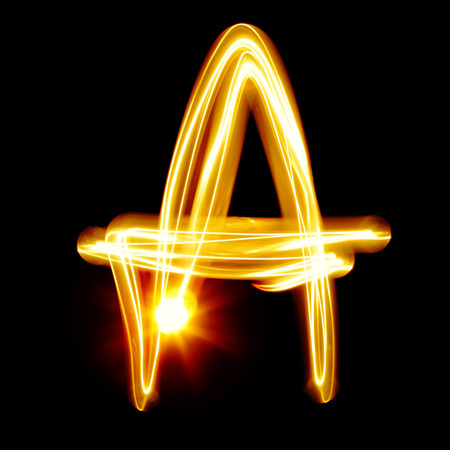 fire font: A - Created by light alphabet over black background Stock Photo