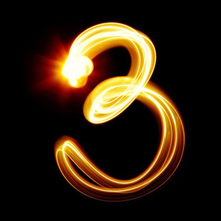 three orange: Three - Created by light numerals over black background Stock Photo