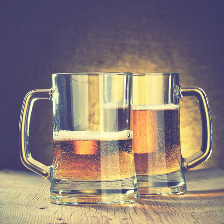 alehouse: Beer mugs on the wooden table. Retro style filtred