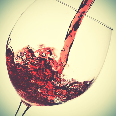 Pouring of red wine in glass. Retro style filtred image