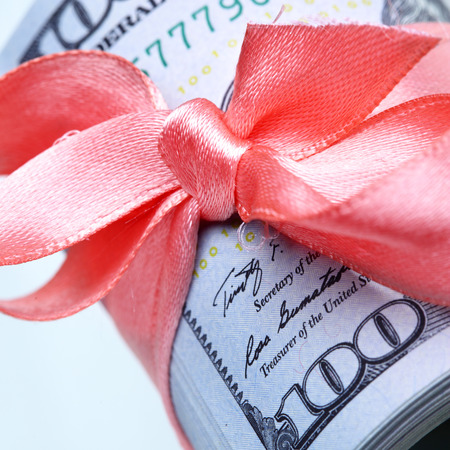 depravity: Roll of dollars with ribbon and bow