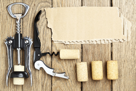 Still life with two cork-screws, wine corks and cardboard for text Stock Photo