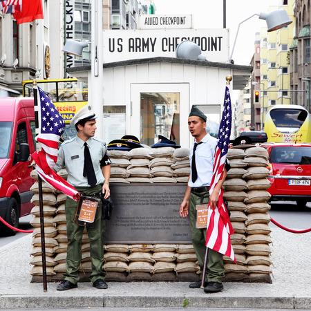 personas en la calle: BERLIN, ALEMANIA - el 22 de de agosto de 2012: Los hombres jóvenes no identificados vestidos de soldados estadounidenses de pie cerca del puesto de control Charlie.The más famoso punto de cruce entre el Este y el Oeste de Berlín después de 2 ª Guerra Mundial. Editorial