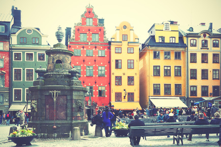 square image: STOCKHOLM, SWEDEN - May 20, 2015: Tourists near the two most famous houses on Stortorget square in Stockholm. Retro style filtered image Editorial