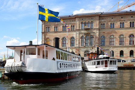 sweden flag: STOCKHOLM, SWEDEN - May 20, 2015: Ferryboats on the berth at Slussen stop in Stockholm