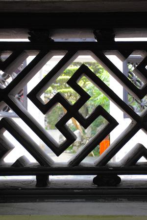 swastika: Swastika - decorative element of bars in ancient Yu Yuan Garden in Shanghai, China. Shallow DOF! Stock Photo