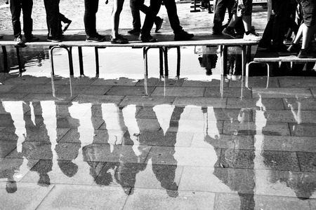 reflection: Walking people reflect in a puddle on San Marco square in Venice, Italy. Black and white image