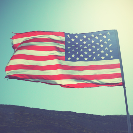 Flag of the United States of America on the wind. Retro style filtered image