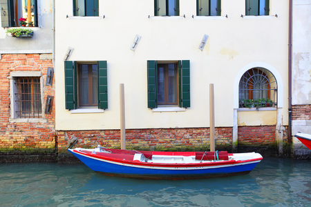 canal house: Boat near house on narrow canal in Venice, italy Stock Photo
