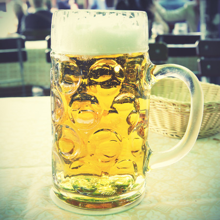 liter: One liter beer mug on a table. Retro style filtered image