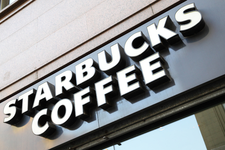 famous industries: MADRID, SPAIN - September 06, 2016: Starbucks coffee shop sign close-up. Starbucks is the largest coffeehouse in the world