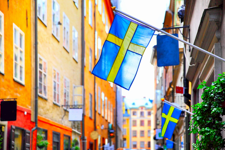 Old street in Stockholm with swedish flags, Sweden. Shallow DOF, focus on the first flag Archivio Fotografico