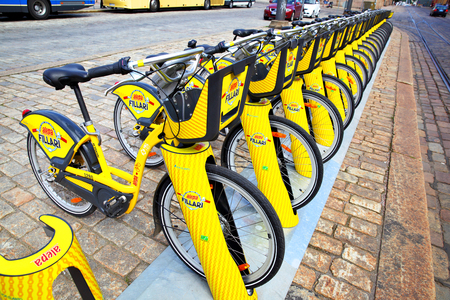 Helsinki, Finland - July 26, 2017: Yellow bicycles at the rental bicycle parking lot in Helsinki