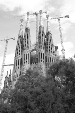 Barcelona, Spain - June 09, 2011:  Bell towers of The La Sagrada Familia cathedral by Antoni Gaudi in Barcelona. Black and white image Редакционное
