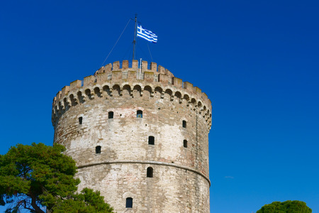 The White Tower in Thessaloniki with waving Greek flag, Greece