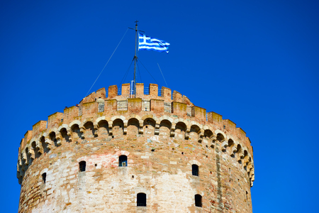 The White Tower in Thessalonica and waving Greek flag, Greece Editorial