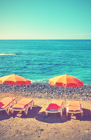 Umbrellas and chaise longues on a sea beach, Tenerife. Retro style filtered image