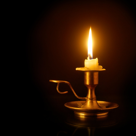 Burning candle on the old brass candlestick over black background 스톡 콘텐츠