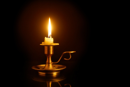 Burning candle on old brass candlestick over black background 스톡 콘텐츠