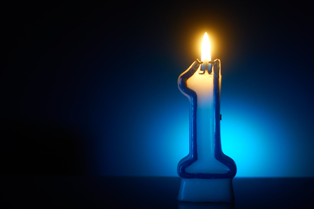 Number One - Burning birthday candle on blue background 写真素材
