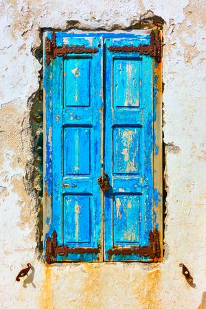 Ventana vieja cerrada con persianas azules en mal estado, Mykonos, Grecia Foto de archivo