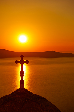 Silhouette of the dome with cross in Santorini at sundown, Greece