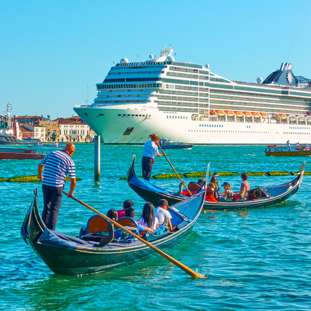 Venice, Italy - June 16, 2018: Large cruise ship and gondolas near waterfront in Venice