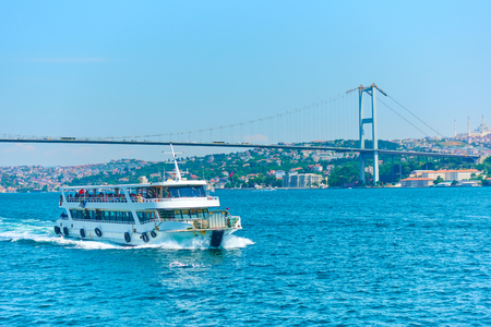 Ferry and 15 July Martyrs Bridge over Bosporus in Istanbul, Turkey