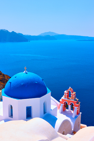 View with Greek orthodox church with blue domes and small belfry in Oia in Santorini island, Greece Stock Photo