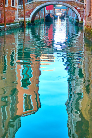 Venetian mirror - Houses, blue sky and small bridge reflect in the water of a side canal. Venice in water reflections