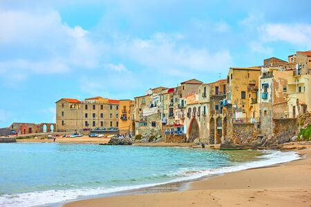 Sandy beach and old houses by the sea in Cefalu, Sicily, Italy